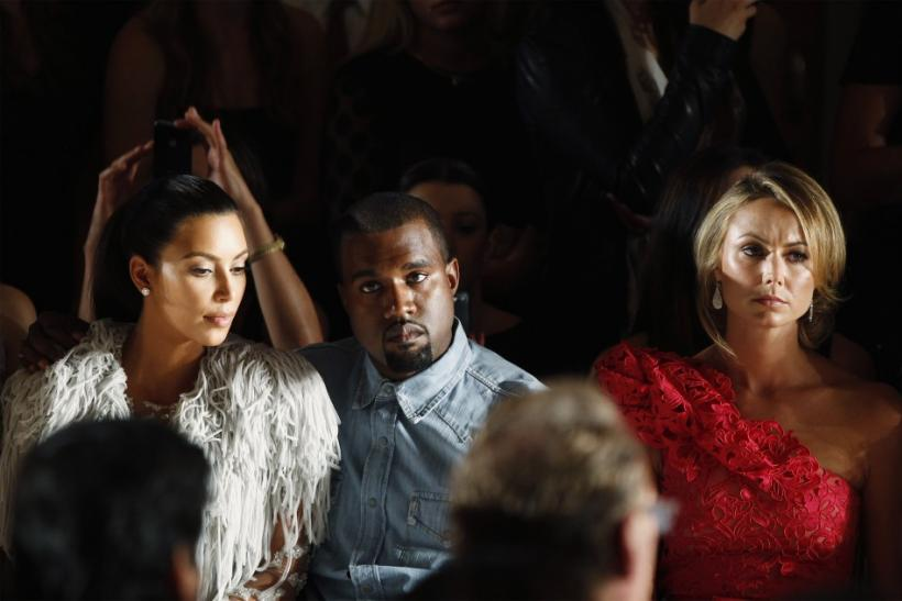 Kanye West drapes his arm over the shoulder of Kim Kardashian (L) as they watch a showing of the Marchesa Spring/Summer 2013 collection during New York Fashion Week, September 12, 2012.