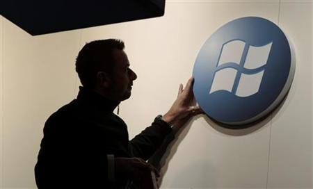A worker adjusts a logo on the Microsoft stand at the CeBIT computer fair in Hanover