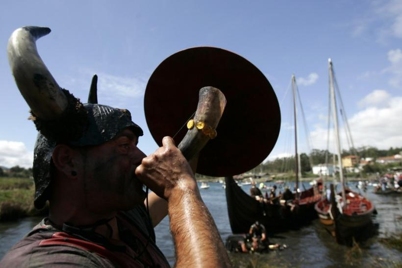 A participant dressed up as a Viking blows a horn as he takes part in the annual Viking festival of Catoira in north-western Spain