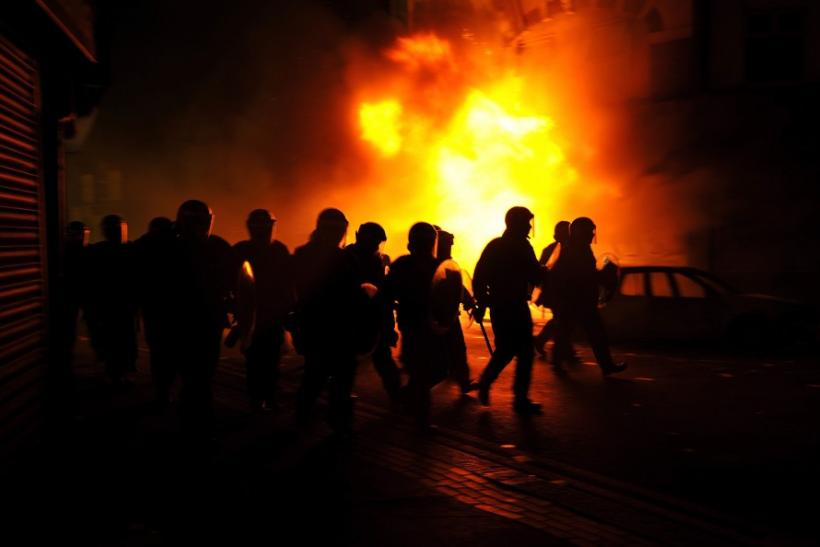 Riot police charge past burning buildings on a residential street in Croydon, south London August 8, 2011