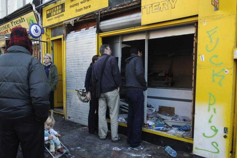 Passersby peer into a looted shop broken into during riots in Hackney in London