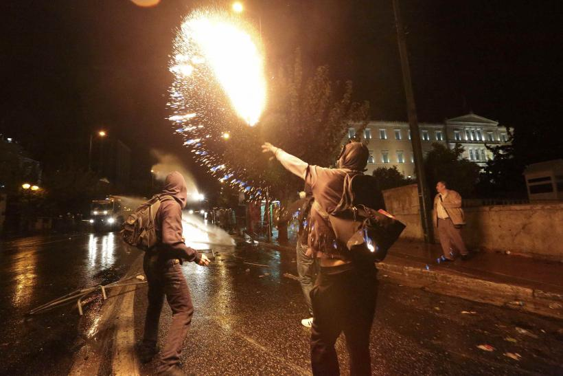 Protester throw a Molotov cocktail at police during massive, violent protest in Athens Wednesday