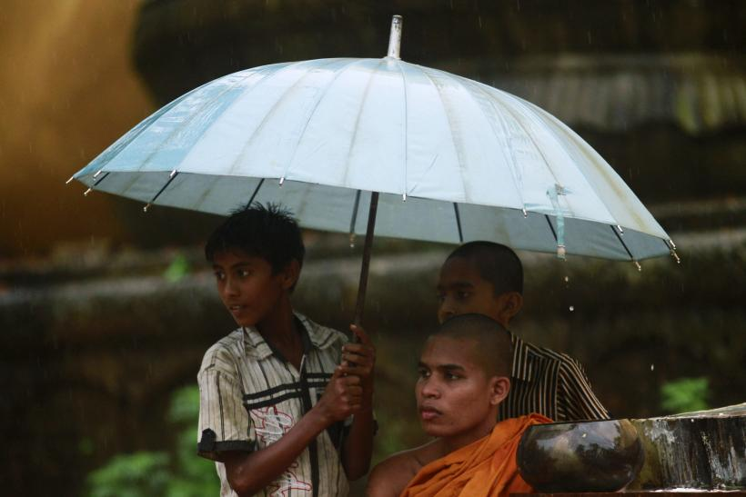 A Bangladeshi Buddhist monk collects alms with children as it rains in Cox's Bazar October 3, 2012, after Muslims attacked and set fire to a temple.