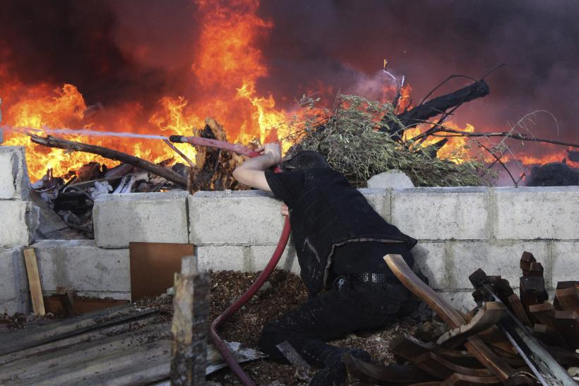 Syrian man tries to put out fire in Jobar, Damascus