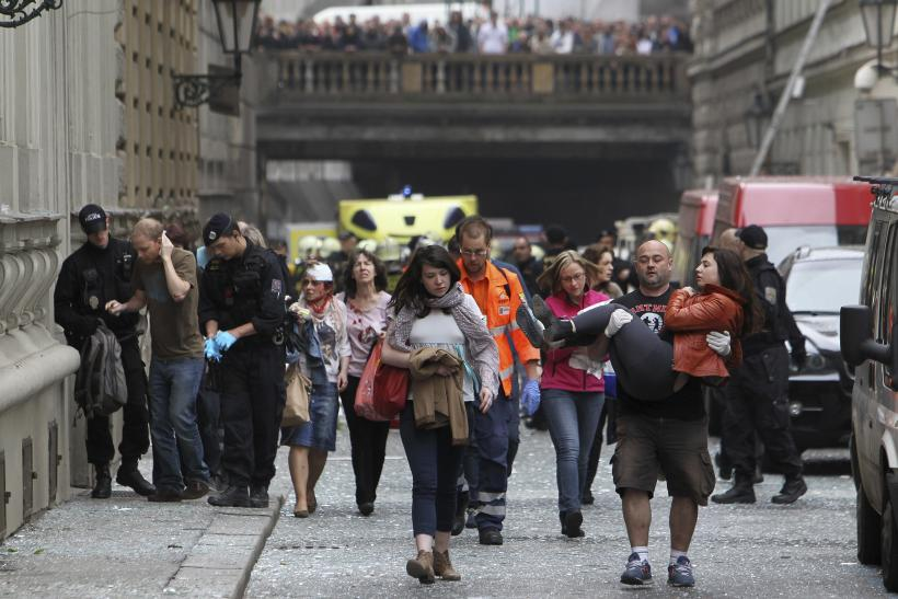 Injured people leave an area in Prague after explosion
