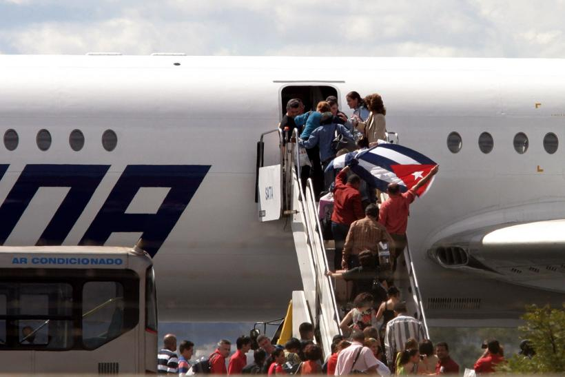 Cuban physicians wave a national flag while boarding a Cuban jet bound for home, from Brasilia,