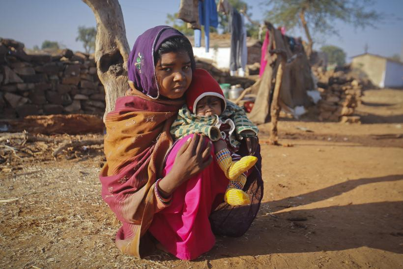 Krishna, 14, sits with her four-month-old baby Alok, outside her house in a village near Baran, located in the northwestern state of Rajasthan,