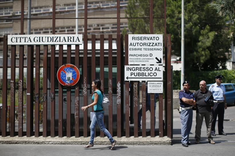 A woman walks past the entrance of the courthouse in Rome June 28, 2013.
