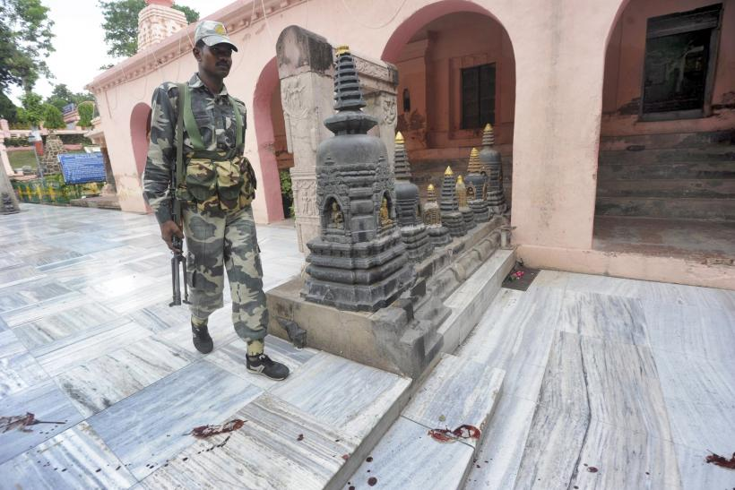 An Indian security personnel walks next to bloody footprints inside the Mahabodhi temple complex, after a series of explosions at Bodh Gaya in the eastern Indian state of Bihar