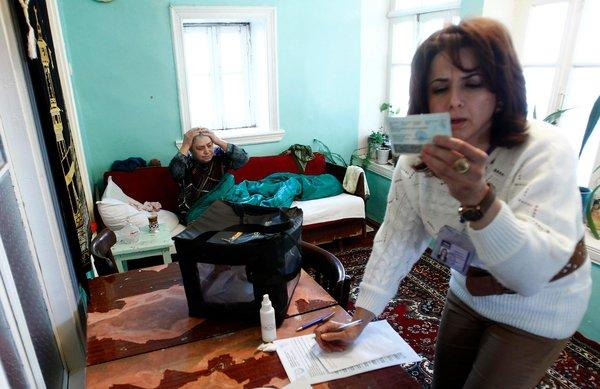 Gulgez Jabrailova, 78, left, waited in her home as an election official checked her ID.