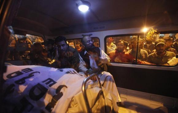 Relatives of Pakistan's Crime Investigation Department (CID) Chief Chaudhry Aslam sit in an ambulance with his body outside Jinnah Postgraduate Medical Centre in Karachi January 9, 2014.