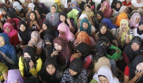 Indonesian workers ready to fly to Saudi Arabia to work as maids wait at a shelter during a police inspection in Bekasi, Indonesia's West Java province.