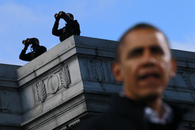 Obama speaks under two counter assault team members