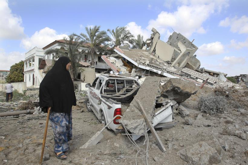 Palestinian walks by home destroyed by Israeli air strike