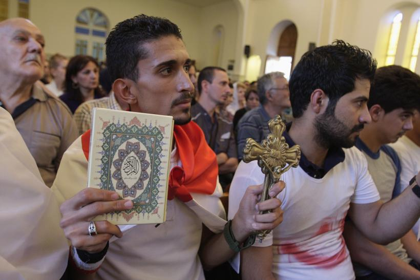 An Iraqi man carrying a cross and a Koran attends a mass at Mar Girgis Church in Baghdad, July 20, 2014.