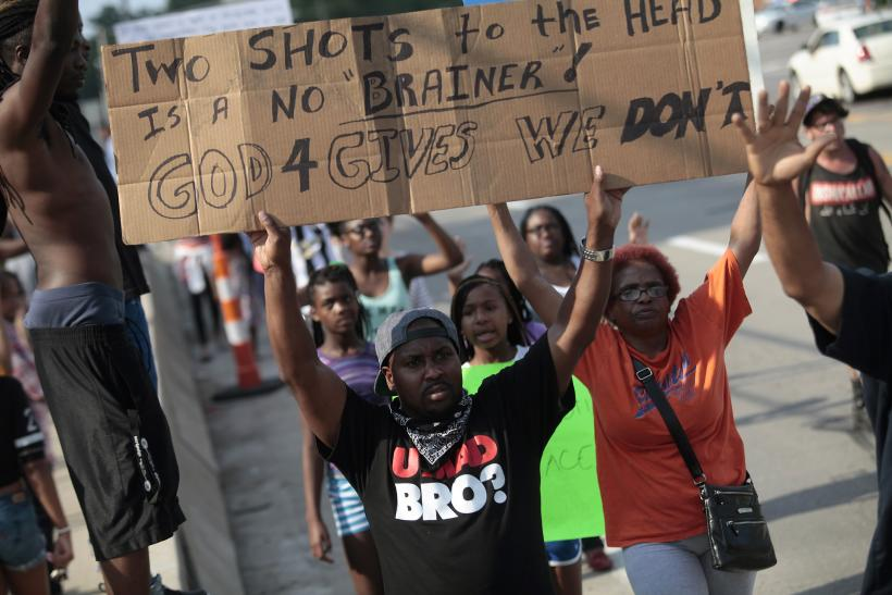 Ferguson protesters hold signs