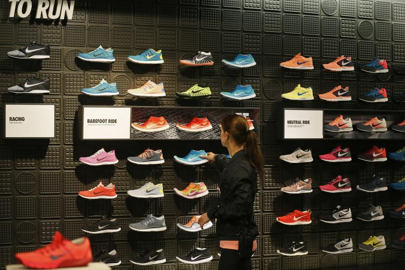 woman picks up a shoe in the Nike store in Santa Monica, California