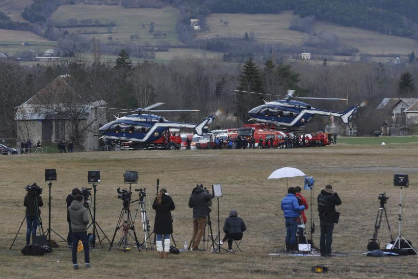 Media gather on an airfield as helicopters from the french gendarmerie